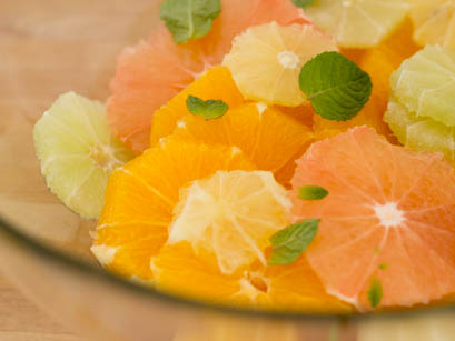 Orange , ginger and mint mixed in a bowl